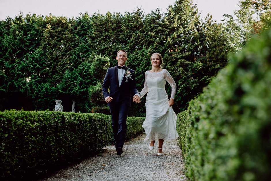 Braut und Bräutigam rennen Hand in Hand
