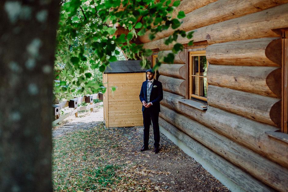 Bräutigam wartet auf die Braut am Holzhaus