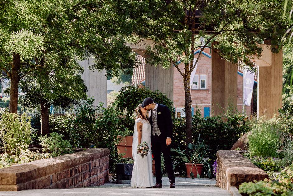 Brautpaar küsst sich unter Bäumen