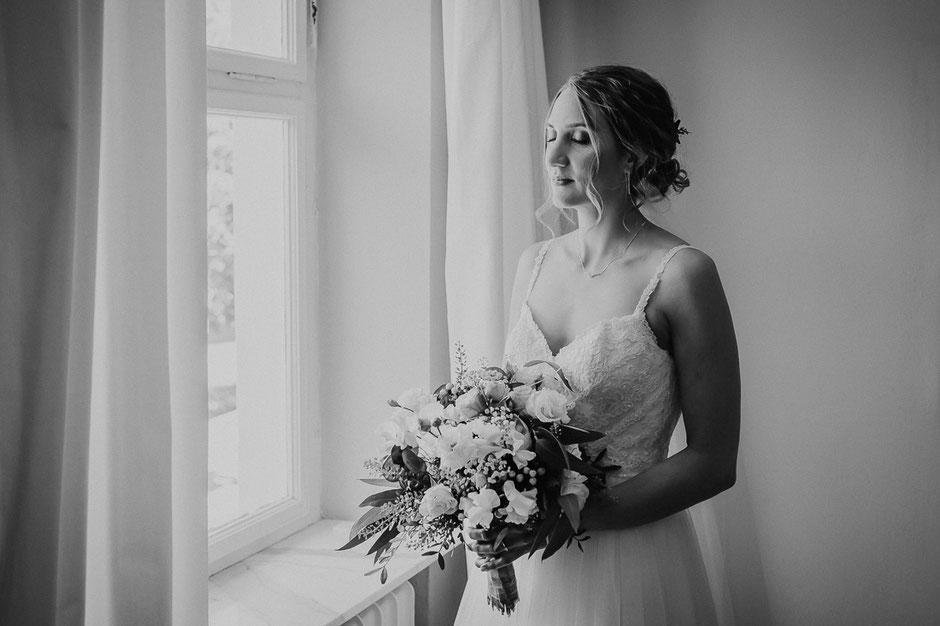 Braut steht vor dem Fenster und wartet auf den First Look mit ihrem Bräutigam