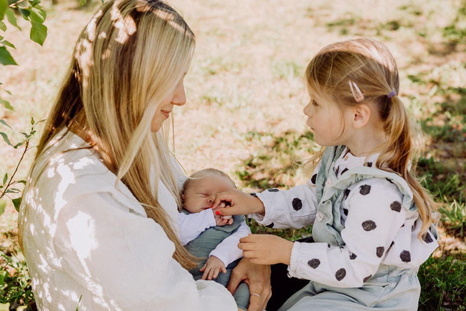 Mutter und Schwester halten die Hand des Neugeborenen