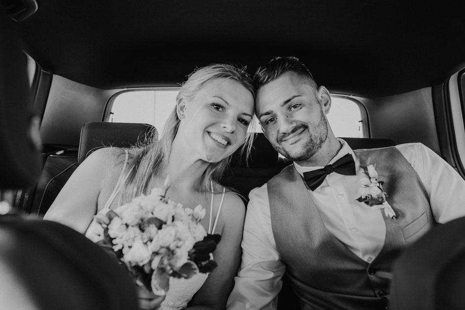 lächelndes Brautpaar sitzt im Hochzeitsauto in Rheinhessen