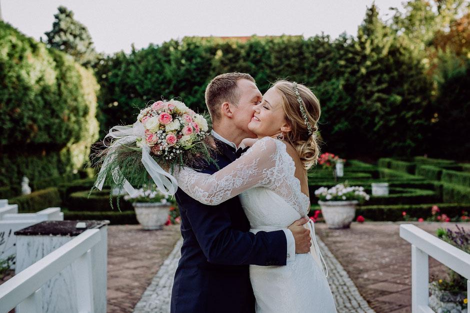 Bräutigam küsst Braut auf die Wange bei Brautpaarshooting in Bissersheim