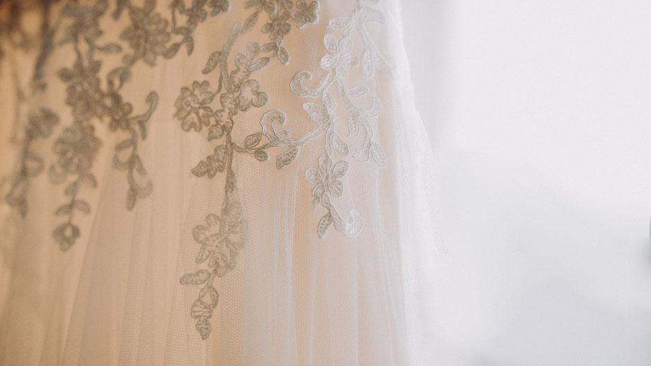 Detailaufnahme der Spitze eines weissen Brautkleids