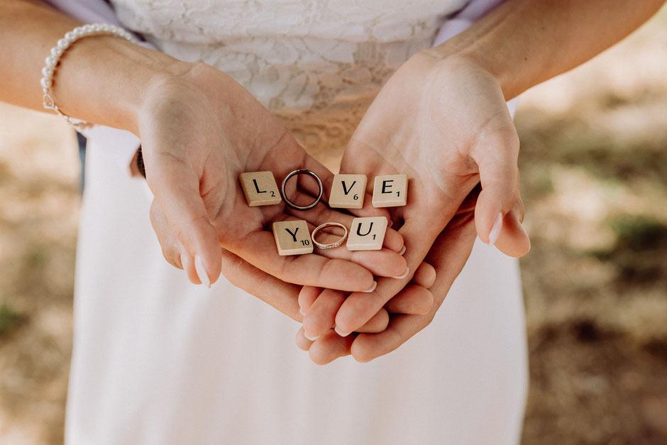 Brautpaar hält Eheringe in den Händen