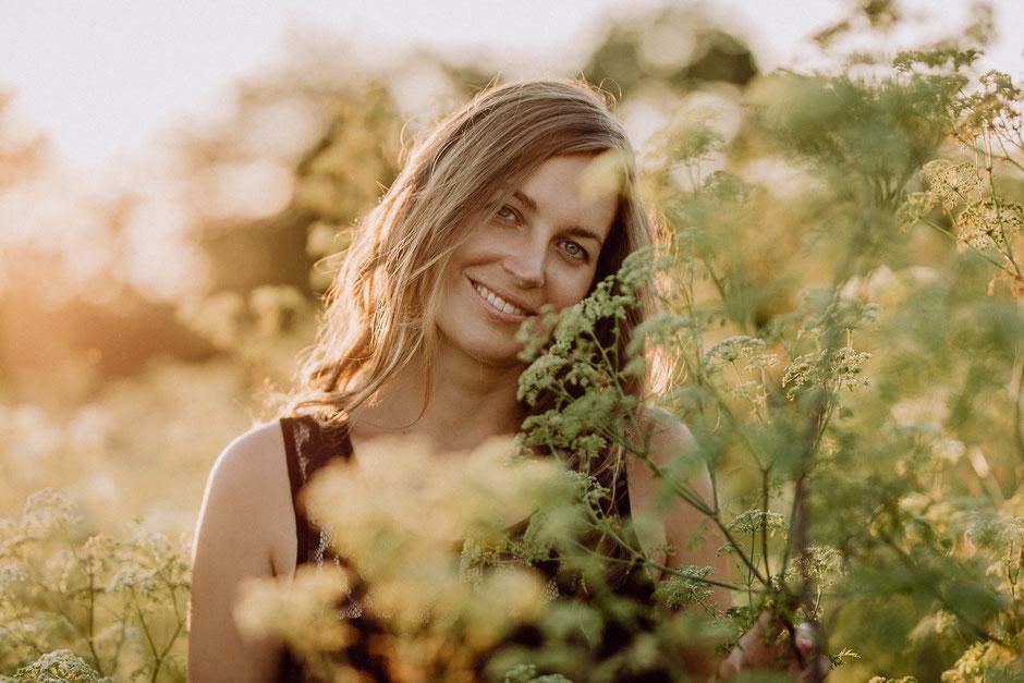 junge Frau steht zwischen hohen Pflanzen auf einem Feld und lächelt
