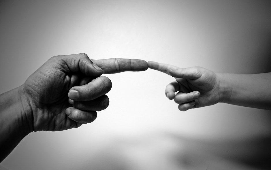 Zwei Finger die sich berühren und Vertrauen und Hilfe zeigen