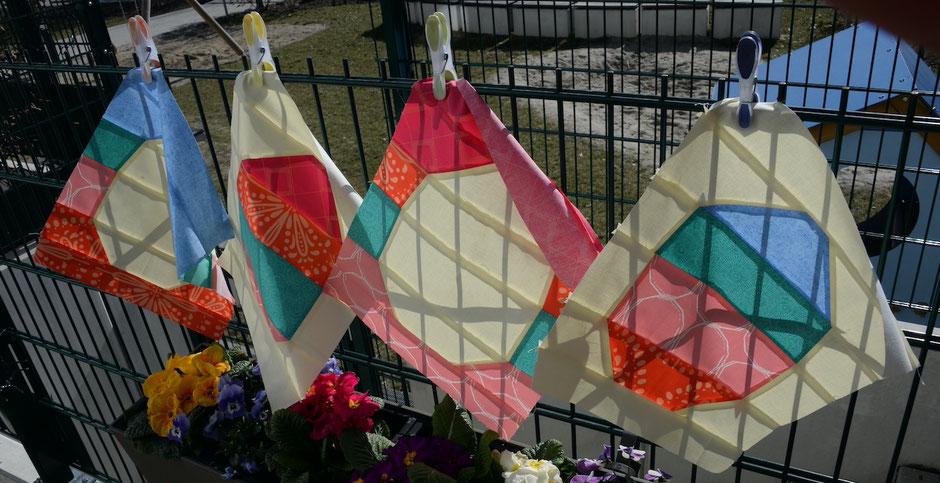 4 Patchwork Ostereier, aufgehängt am Zaun mit Blumen