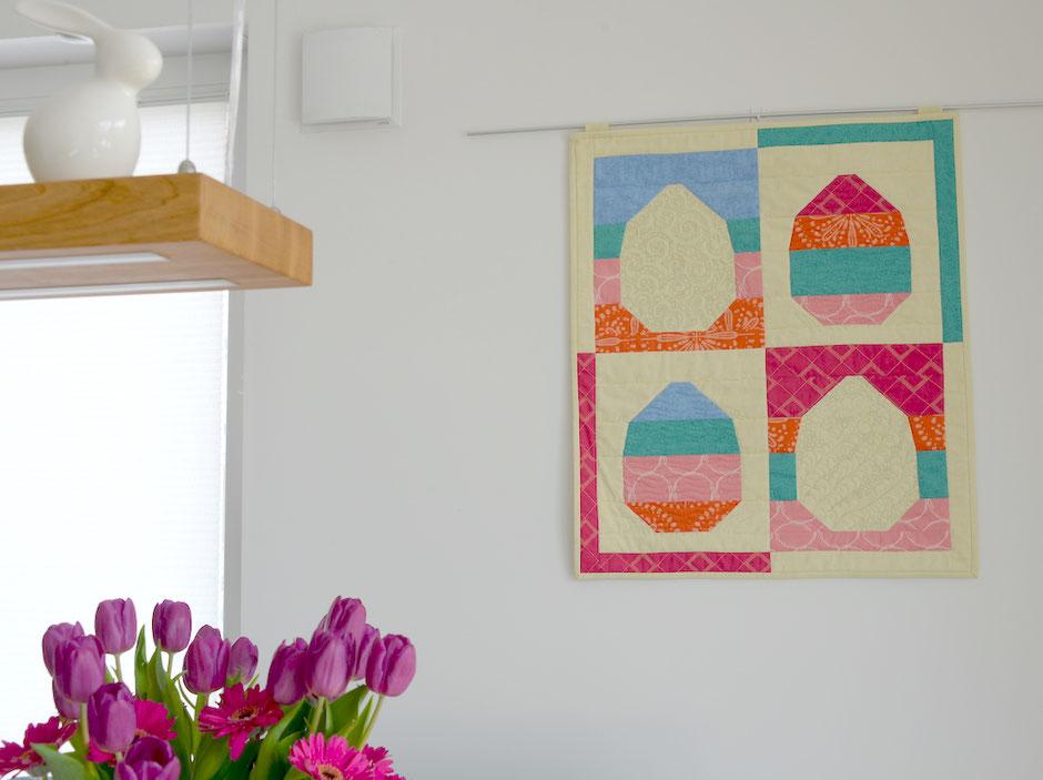 Osterei Quilt an der Wand, lila Tulpen im Vordergrund
