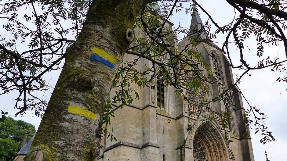 Photo de la basilique d'Avioth avec en avant plan le signe du balisage du chemin de Saint-Jacques de  Compostel peint sur un arbre
