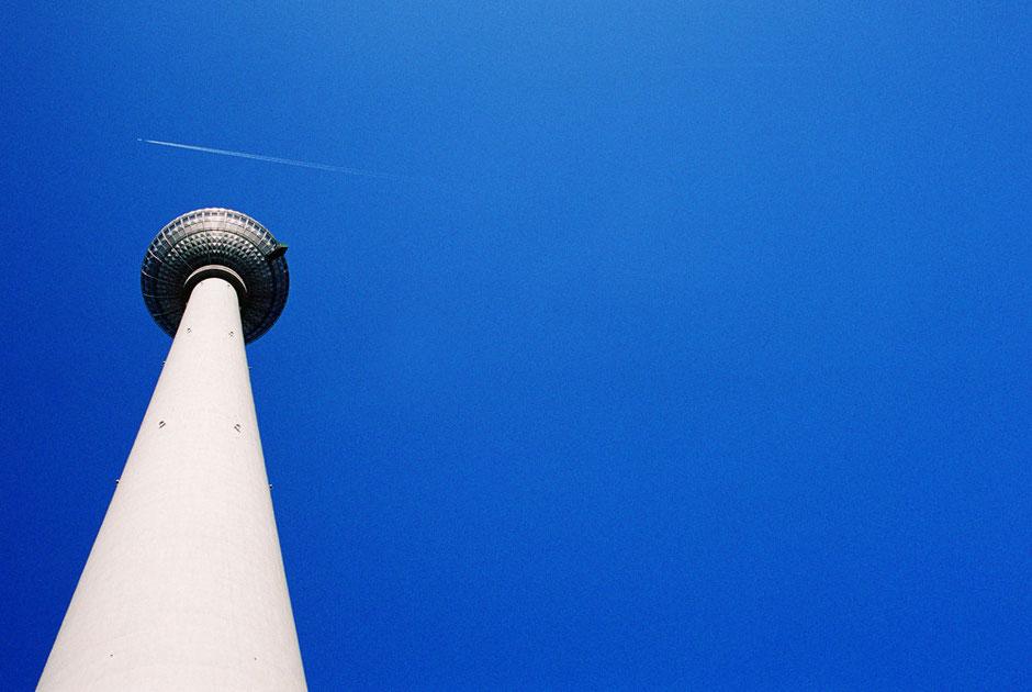 Berlin Mitte Alexanderplatz Fernsehturm vor blauem Himmel mit Flugzeug