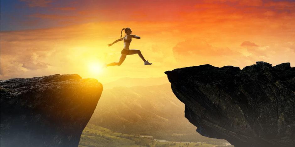 Mujer saltando entre dos precipicios como alegoría de la superación del deporte