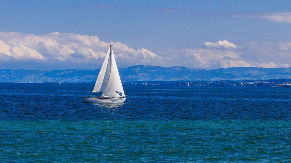 Deutschland-Tourismus: Ein Segelboot segelt einsam auf dem Bodensee. Im Hintergrund die Berge.