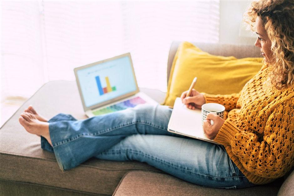 Frau mit blonden Haaren, Jeans und gelben Pullover sitzt mit Block und Kaffeetasse auf dem Schoss, schaut in einen Laptop zum Online-Abschluss der Seminar-Versicherung ERGO