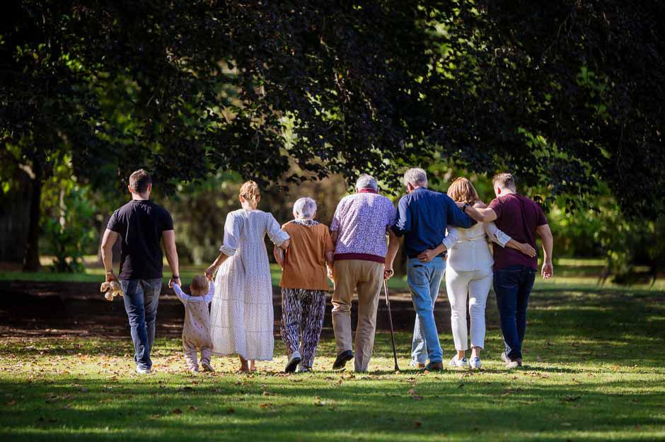 grosse-familie-laeuft-nebeneinander-im-park-mehrgenerationen-fotoshooting-familienbilder-oma-opa-grosseltern-kinder-familienfotos-duesseldorf-duisburg
