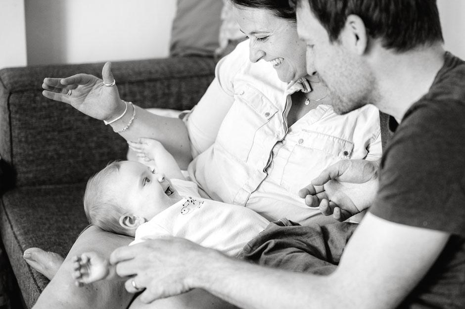 froehliches-baby-liegt-auf-schoss-der-eltern-familienfotos-familienshooting-mit-baby-zu-hause-familienbilder-duesseldorf-duisburg