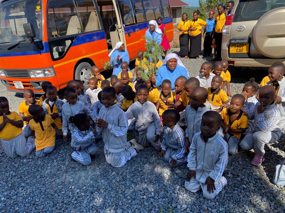 Kinder und Schwestern knien nieder um Danke zu sagen für ihren Schulbus.