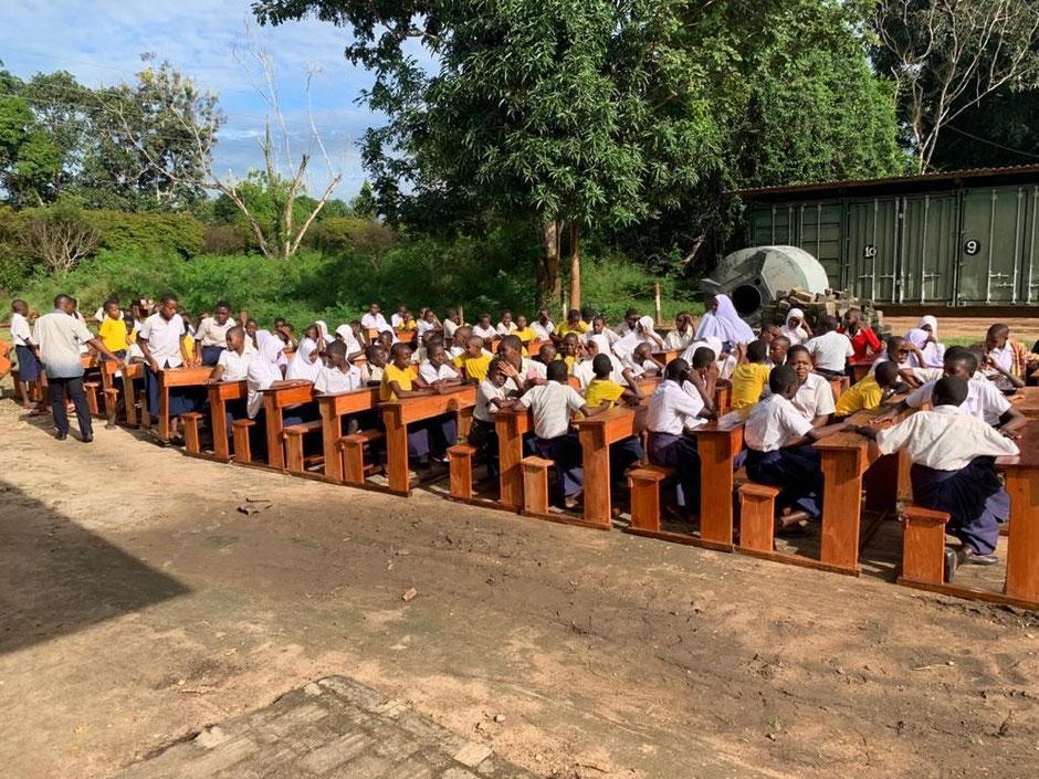 Die Landshuter gemeinnützige Familienstiftung Pöschl hat aus dem Unterricht auf dem Fußboden strahlende Kinder auf Schulbänken gemacht und für sieben renovierte Klassenzimmer die Schulbänke gestiftet. Gefertigt in unserer Schreinerei in Kilimahewa.