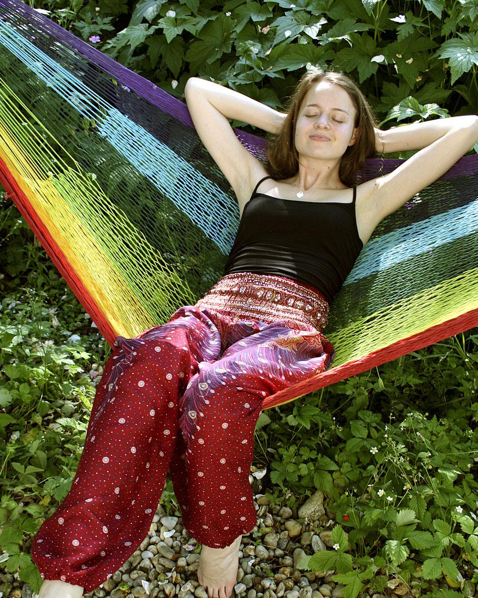 Schöne Frau mit Haremshose, Yogahose, Pluderhose (mit Paisley- und Pfauenfeder-Muster, pink, Fairtrade) entspannt in der Hängematte