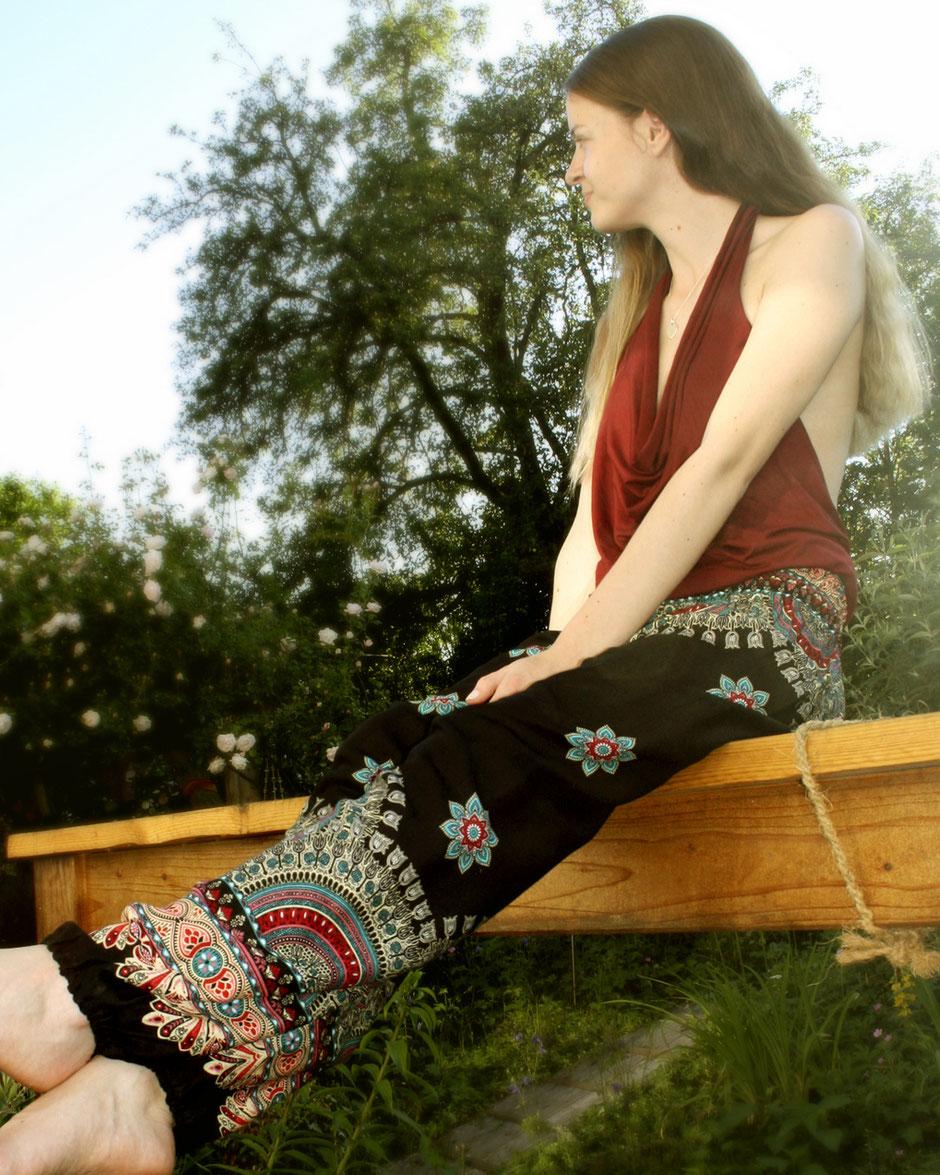 Model mit Haremshose, Yogahose, Pluderhose (Mandala und Blumen Muster, schwarz, Fairtrade) sitzt enspannt im Garten