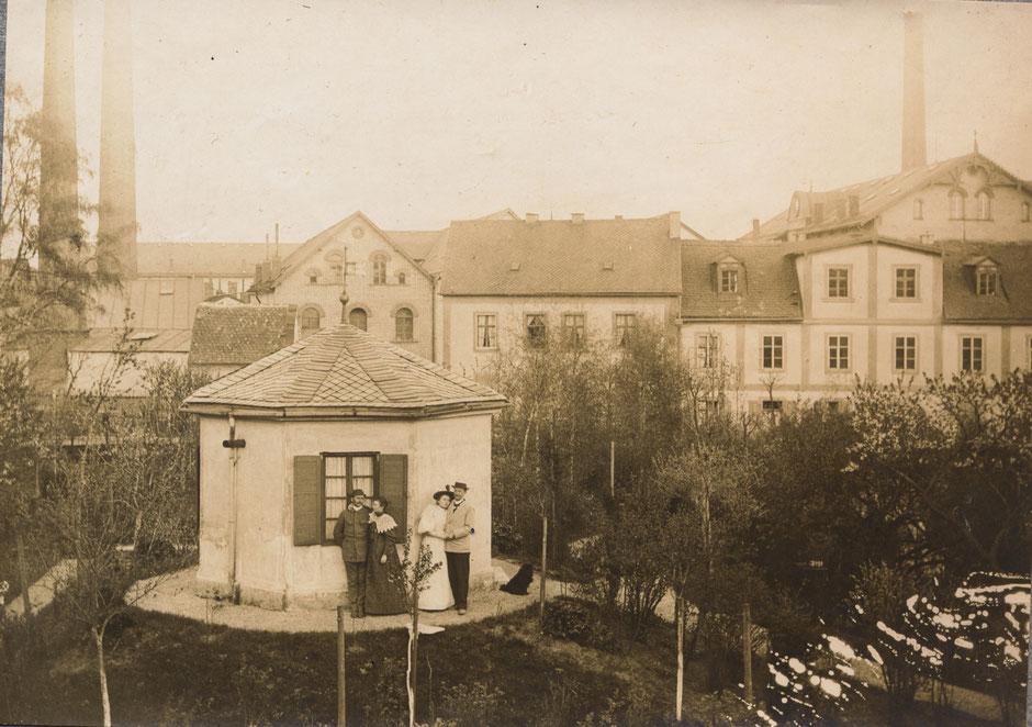 """Vom """"Pfarrhäusl"""" der Blick auf die Fabrik. Die Personen sind nicht bekannt. (vor 1903, da noch altes Wohn/Bürogebäude)"""