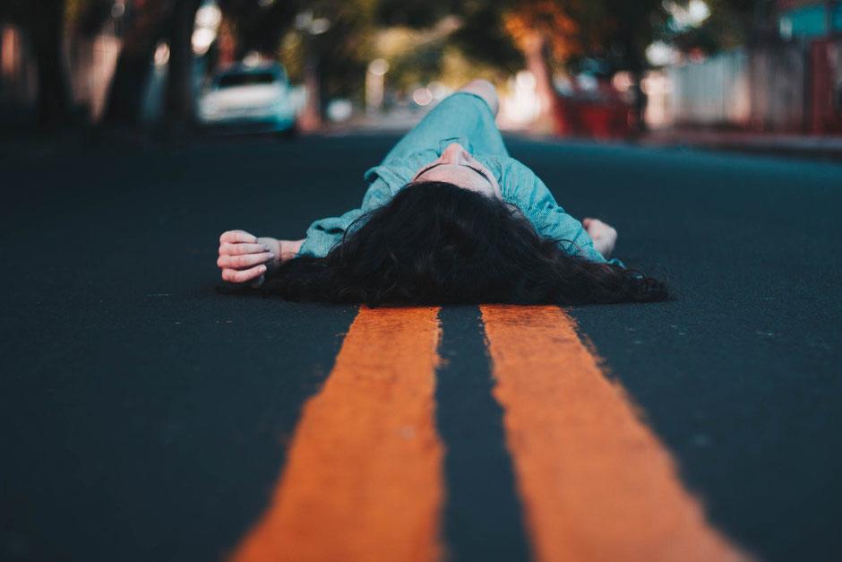 Frau liegt auf Straße
