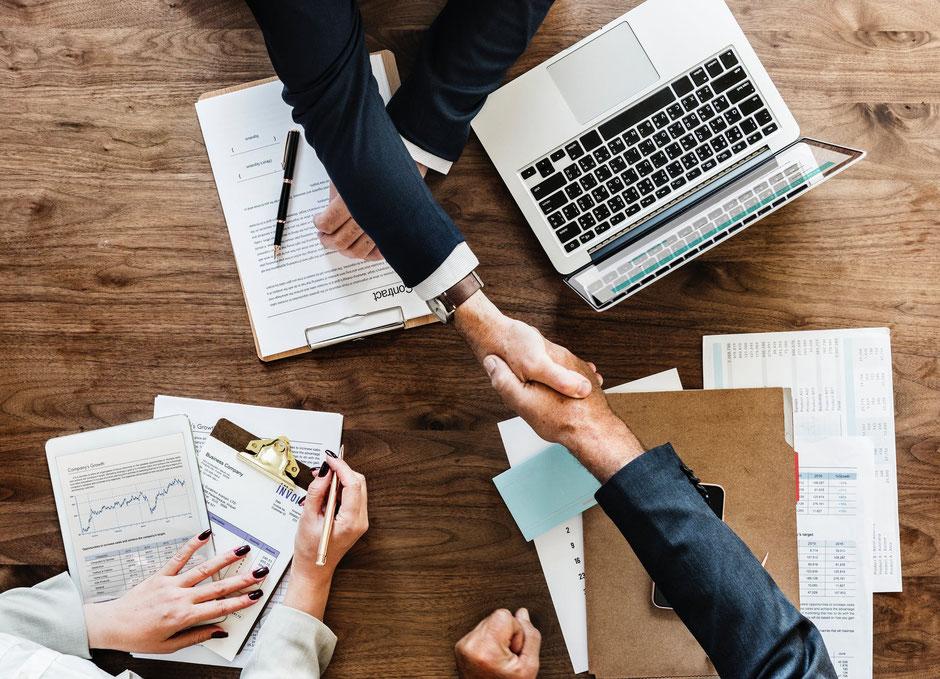Menschen geben einander Hand am Arbeitsplatz
