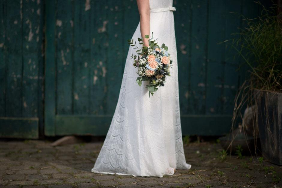 Eine Braut hält einen Brautstrauß. Mark Dillon Photographie