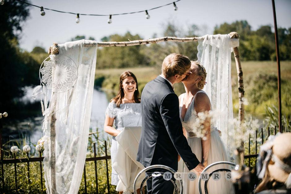 Das Brautpaar küsst sich bei der freien Trauung mit Lisa Wötzel.