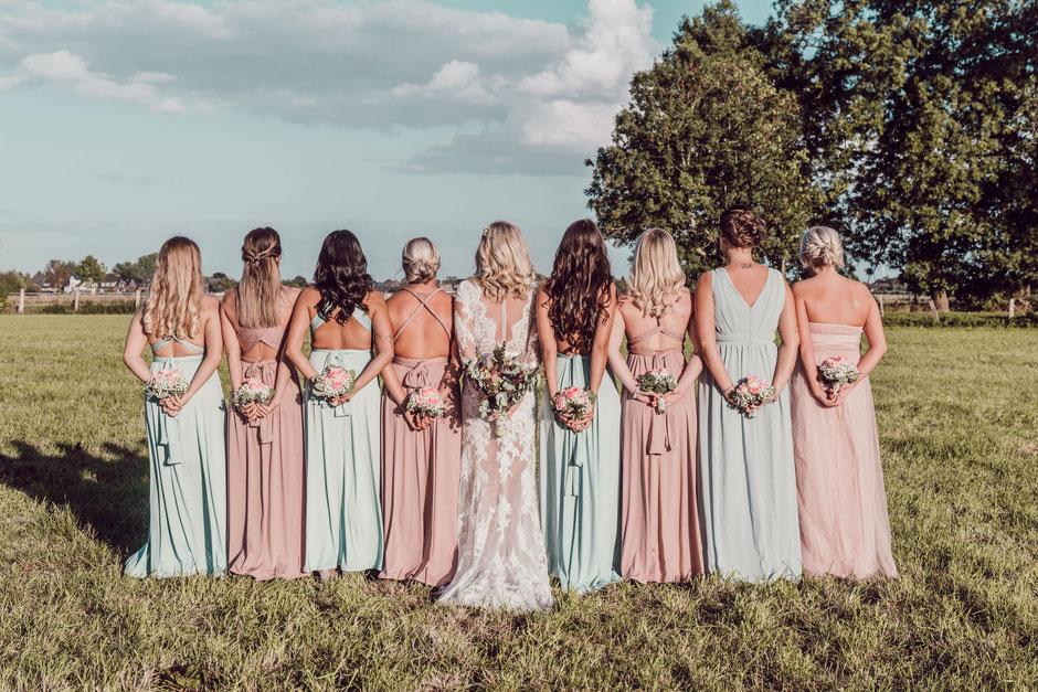 Die Braut steht mit acht Brautjungfern mit dem Rücken zum Fotografen.