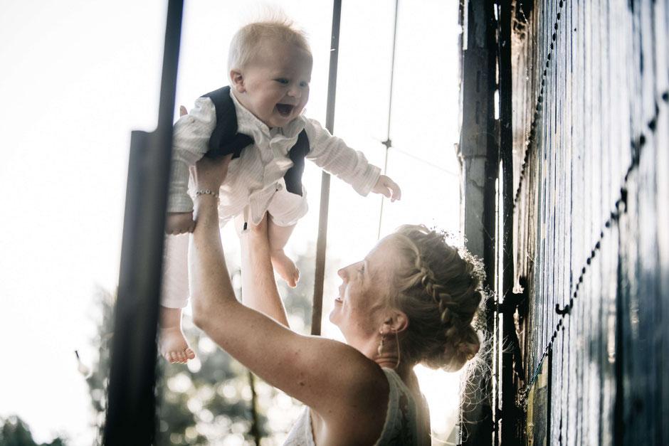 Die Braut hält ihr Baby bei einem Willkommensfest hoch.