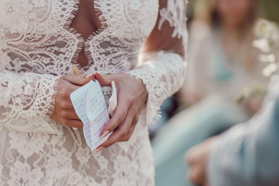 Die Braut hält einen handgeschrieben Zettel in der Hand