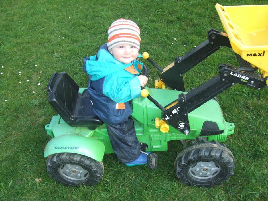 Kind am Trettraktor am Biobauernhof Stadler
