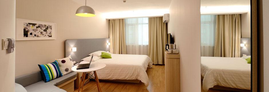 Hotelzimmer von innen mit Bett, Tisch und Sitzgelegenheit
