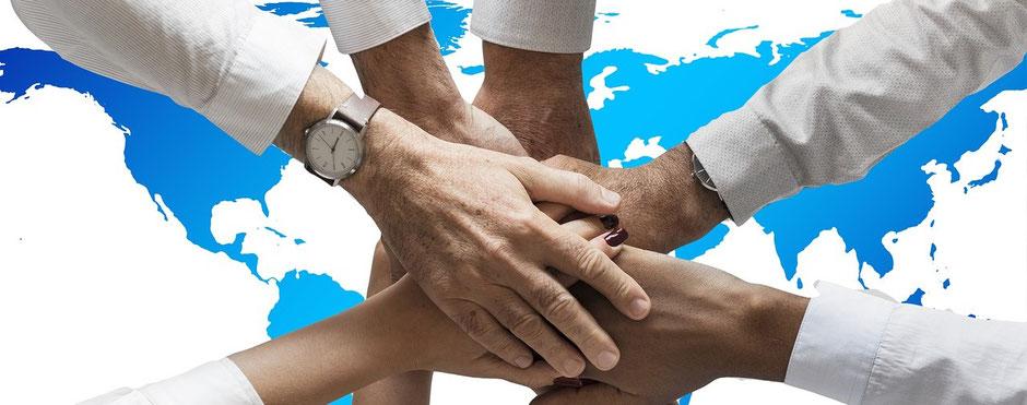 Mehrere Hände fassen sich vor einer Weltkarte an und symbolisieren einen Zusammenschluss