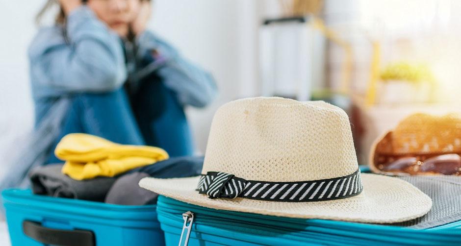 Eine Frau mit gepackten Koffern ist traurig, weil sie nicht in den Urlaub kann wegen Coronavirus-Quarantäne. Zum Glück ist sie gut abgesichert mit der günstigen Covid-19-Reiseversicherung.