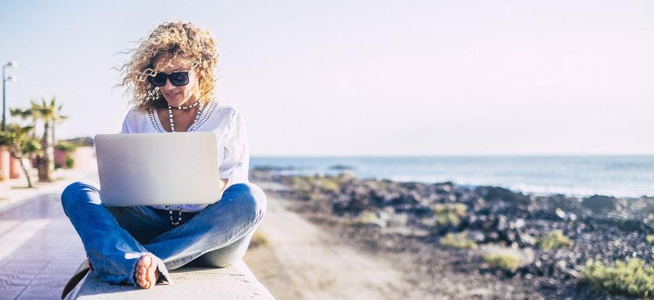 Junge Frau mit Laptop am Strand. Workation liegt im Trend. Dazu die passende Langzeit-Krankenversicherung der ERGO.