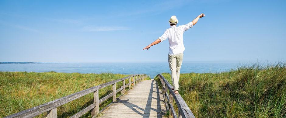Ein Mann balanciert auf einem Geländer auf dem Weg zum Meer als Sinnbild für Urlaub in Deutschland und ein Kooperations-Angebot der ERGO Reiseversicherung mit Gastgebern