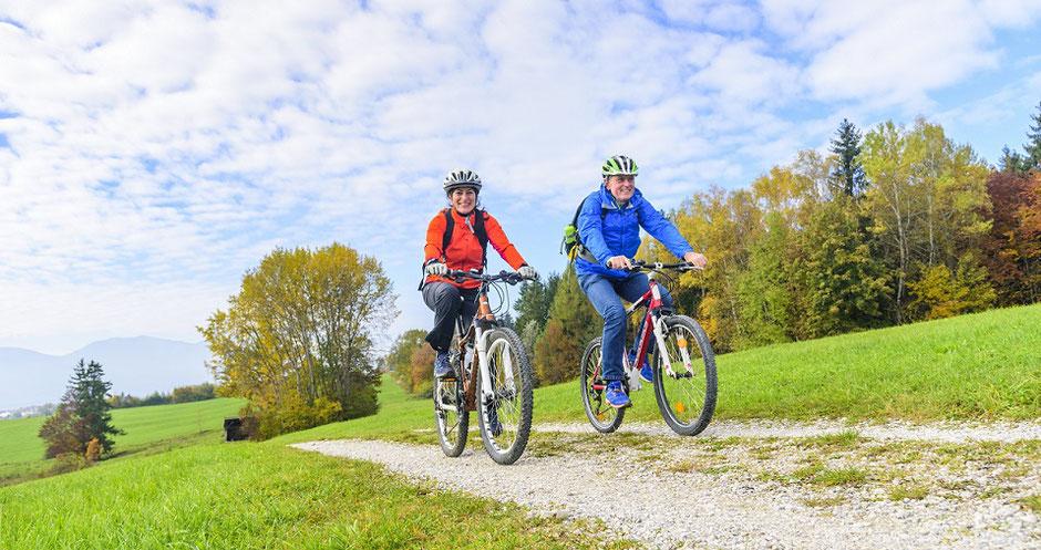 Ein Pärchen radelt durch idyllische Landschaft. Urlaub in Deutschland ist beliebt, besonders gut geschützt mit einer Reiserücktritts-Versicherung für Tourismus in Deutschland mit Corona-Schutz.