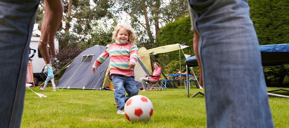 Ein  Mädchen spielt Fußball auf dem Campingplatz und lacht. Die Eltern haben eine Camping-Reiserücktritts-Versicherung bei der ERGO mit Corona abgeschlossen.
