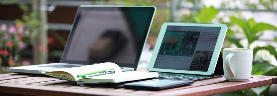 Laptop, Tablet, Notizbuch, Stift und Kaffeetasse zur Versicherung-Schadenbearbeitung
