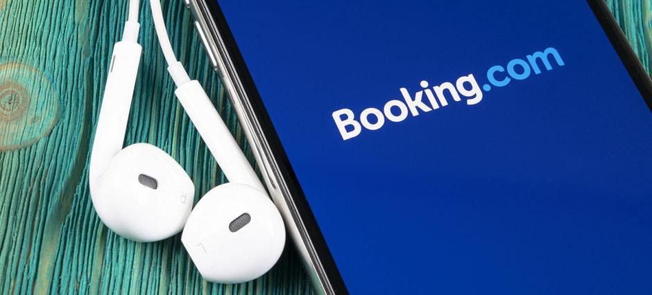 iPhone mit Booking-com-Icon und Logo. Dazu Kopfhörer. Am besten zur Hotelbuchung gleich einen Reiseschutz anbieten und verkaufen bei Buchungen über Booking.com und Airbnb.