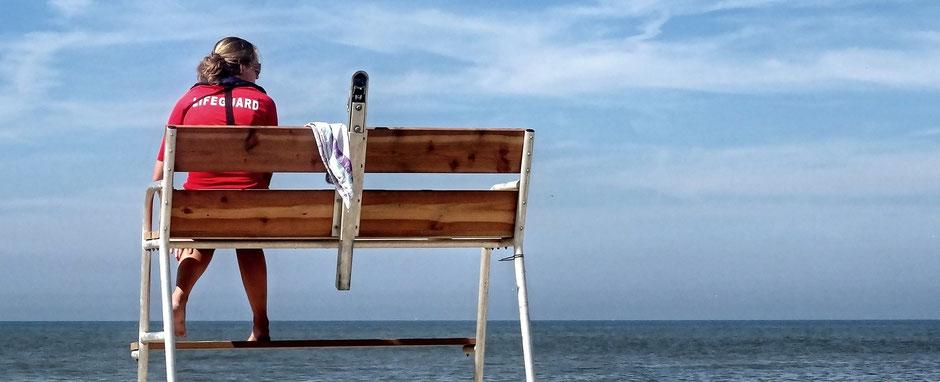 Eine Rettungsschwimmerin sitzt auf einem Hochsitz und schaut aufs Meer