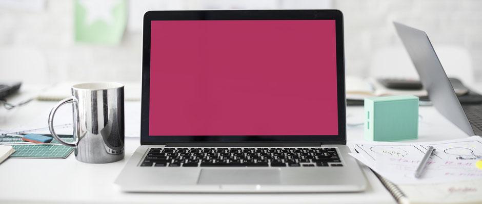 Laptop auf einem Bürotisch mit Kaffeetasse