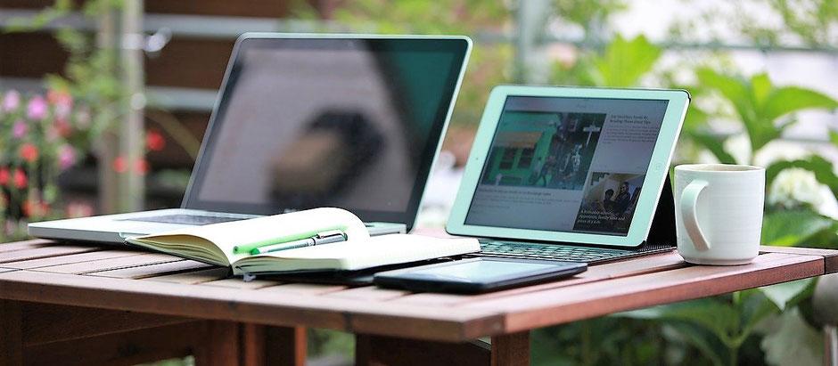 Zwei Notebooks geöffnet, die Angebote zur Reiseversicherung der ERGO mit neuem Corona-Schutz und Quarantäne werden gerade überarbeitet