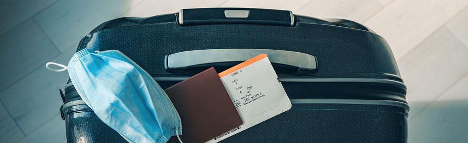 Corona-Urlaub: Koffer mit Maske, Pass und Flugticker für den Urlaub. Nun in Quarantäne zu Hause. Was leistet die ERGO Reiseversicherung im Schadensfall?