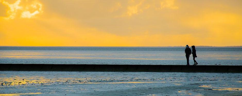zwei Menschen laufen am Strand land - Sonnenaufgang auf Usedom