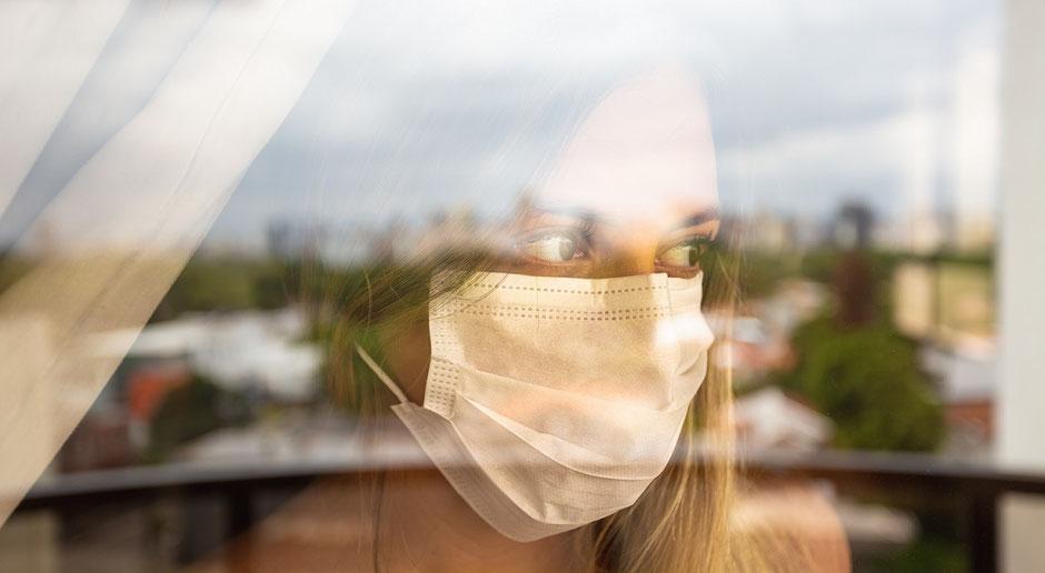 Frau mit Mund-Nasen-Schutz-Maske steht am Fenster eines Hotels und schaut traurig raus, weil sie wegen Corona in Quarantäne ist. Der Ergänzungs-Schutz Covid-19 zahlt die Hotelkosten