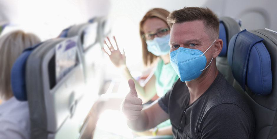 Corona-Urlaub: Frau und Mann im Flugzeug mit Maske auf dem Weg in den Urlaub. Was leistet die ERGO Reiseversicherung beim Ergänzungs-Schutz Covid-19?