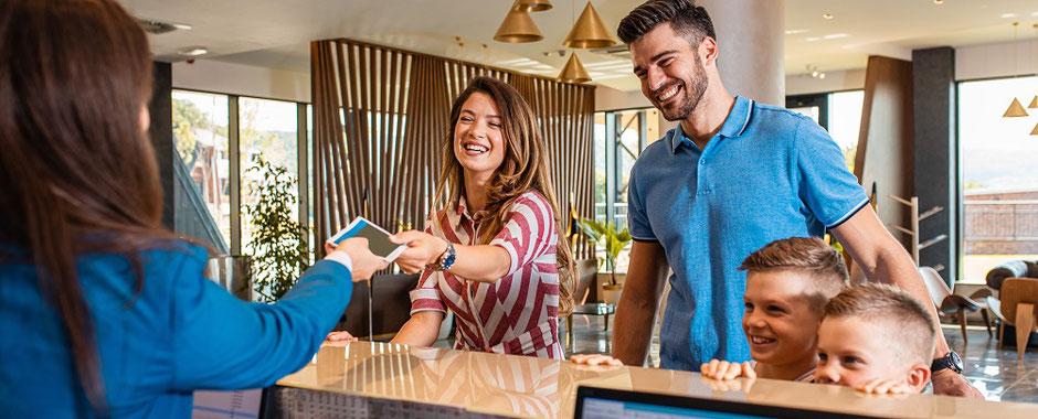 Eine Familie checkt in einem Hotel ein und freut sich auf ihre Ferien und ihren Urlaub in Deutschland mit der passenden Reiseversicherung